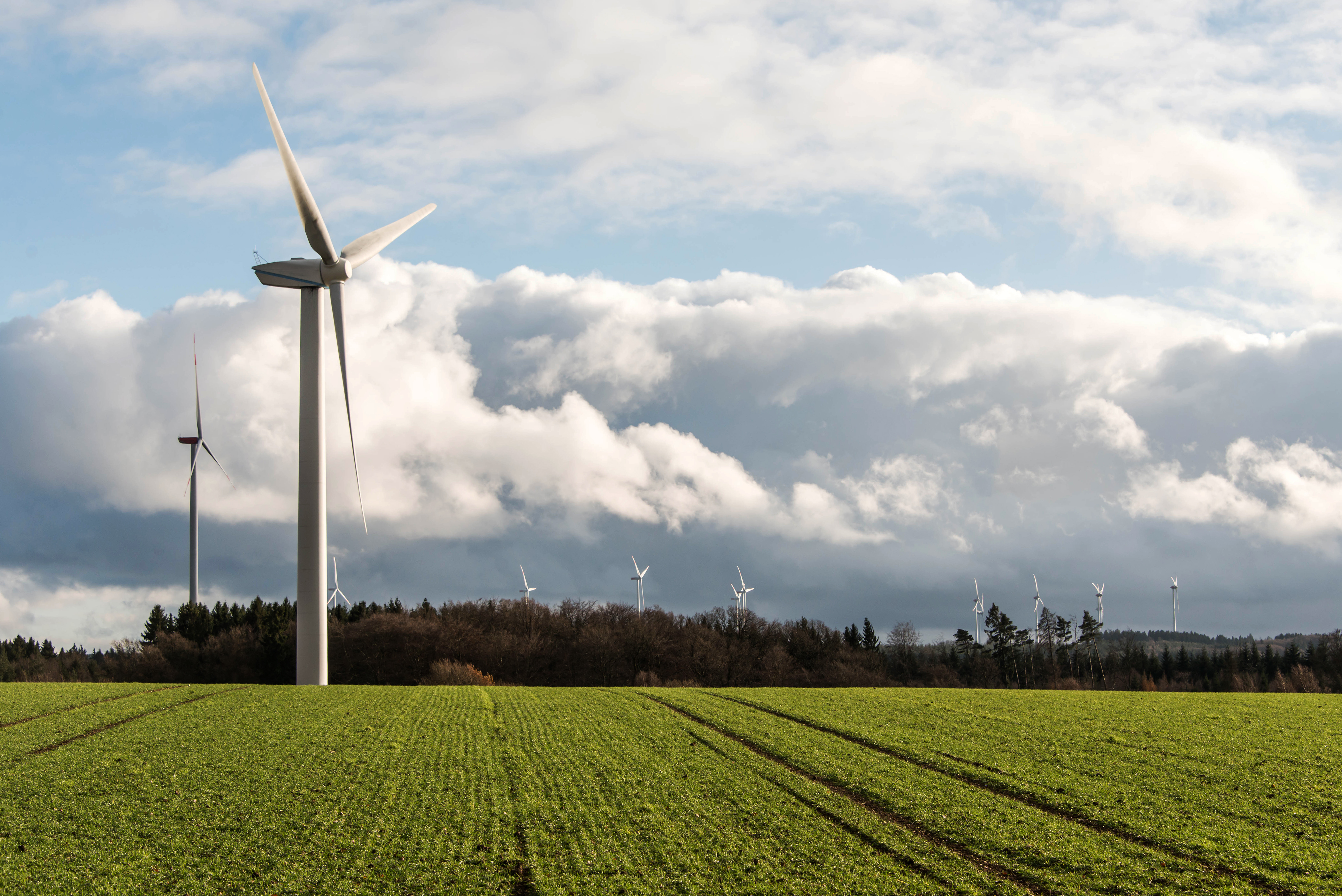 A panorama view over a wind farm landscape in Germany with white generator turbines