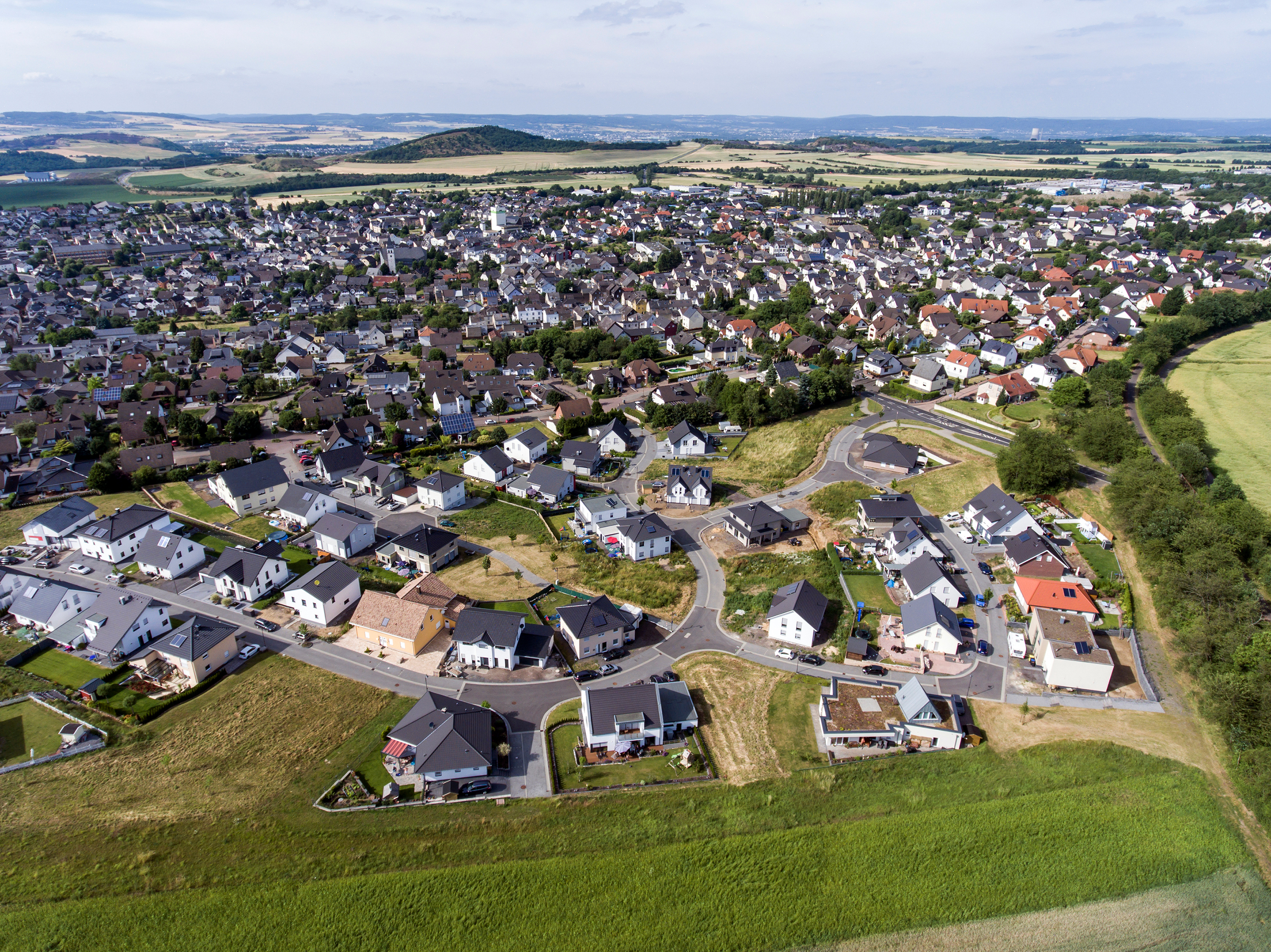 Aerial view of surroundings and the village of Ochtendung in Germany on a sunny summer day with blue sky