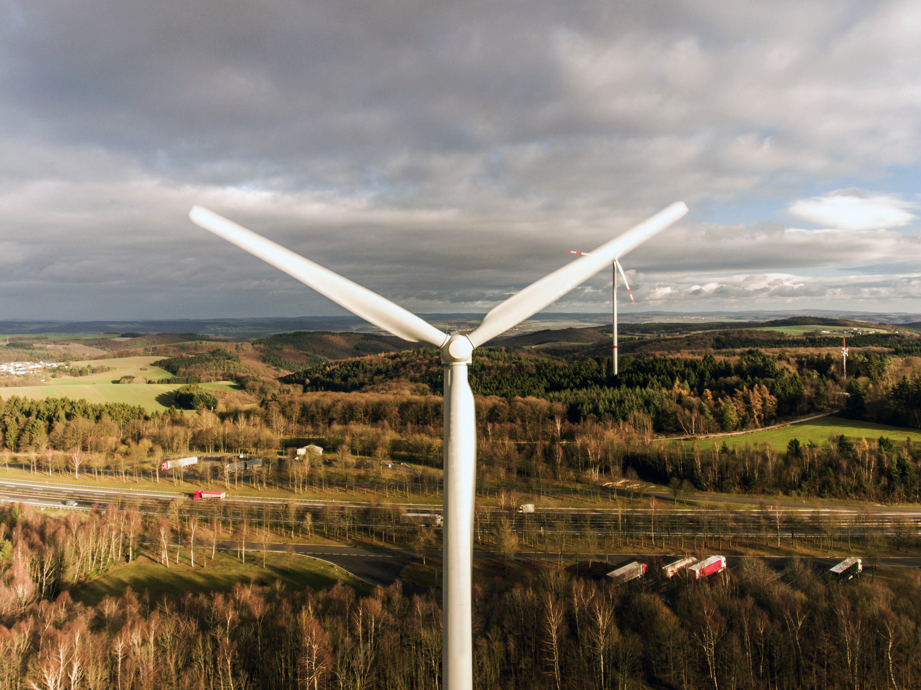 A panorama aerial helicopter view over wind farm landscape in Germany with white generator turbines