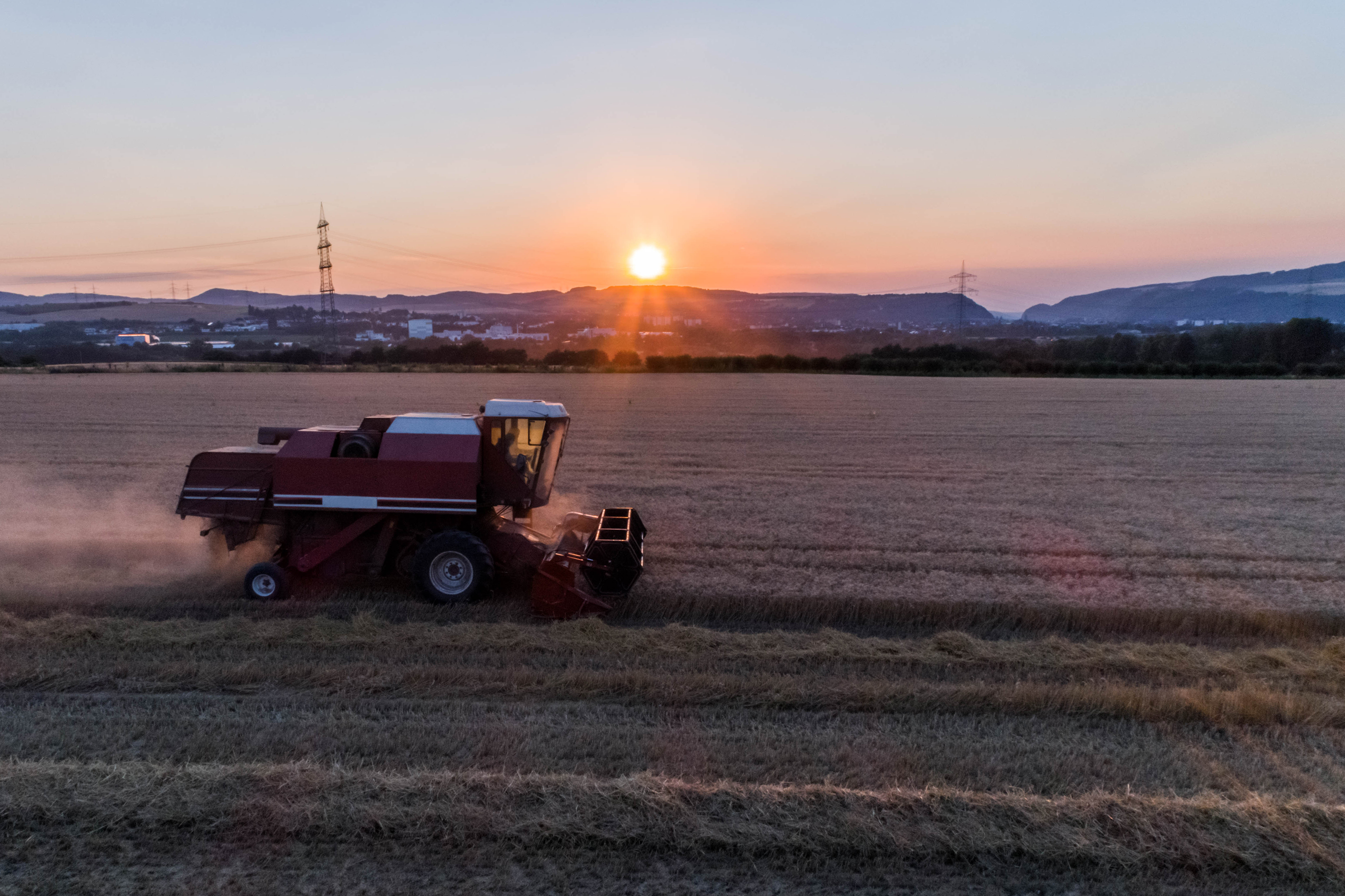 Aerial view of a combine harvester harvesting an oats crop at sunset