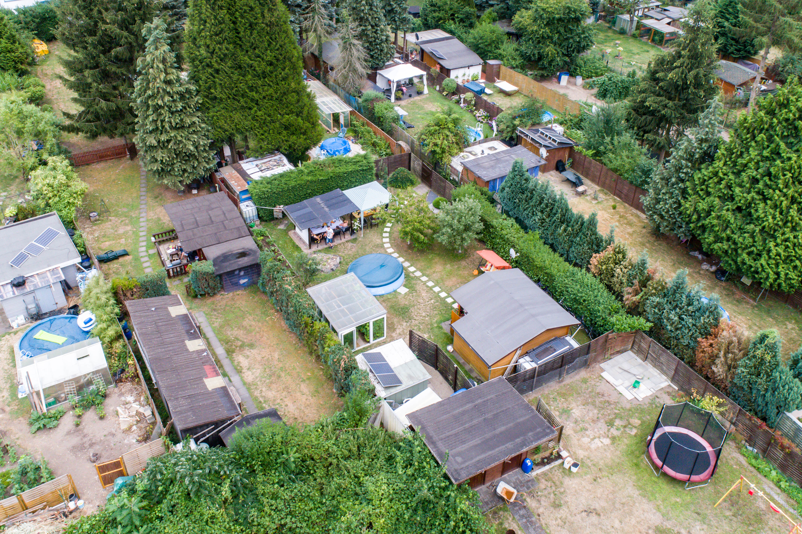 Aerial photo with the drone, a new build-up plot with single houses and gardens, narrow neighbourhood.