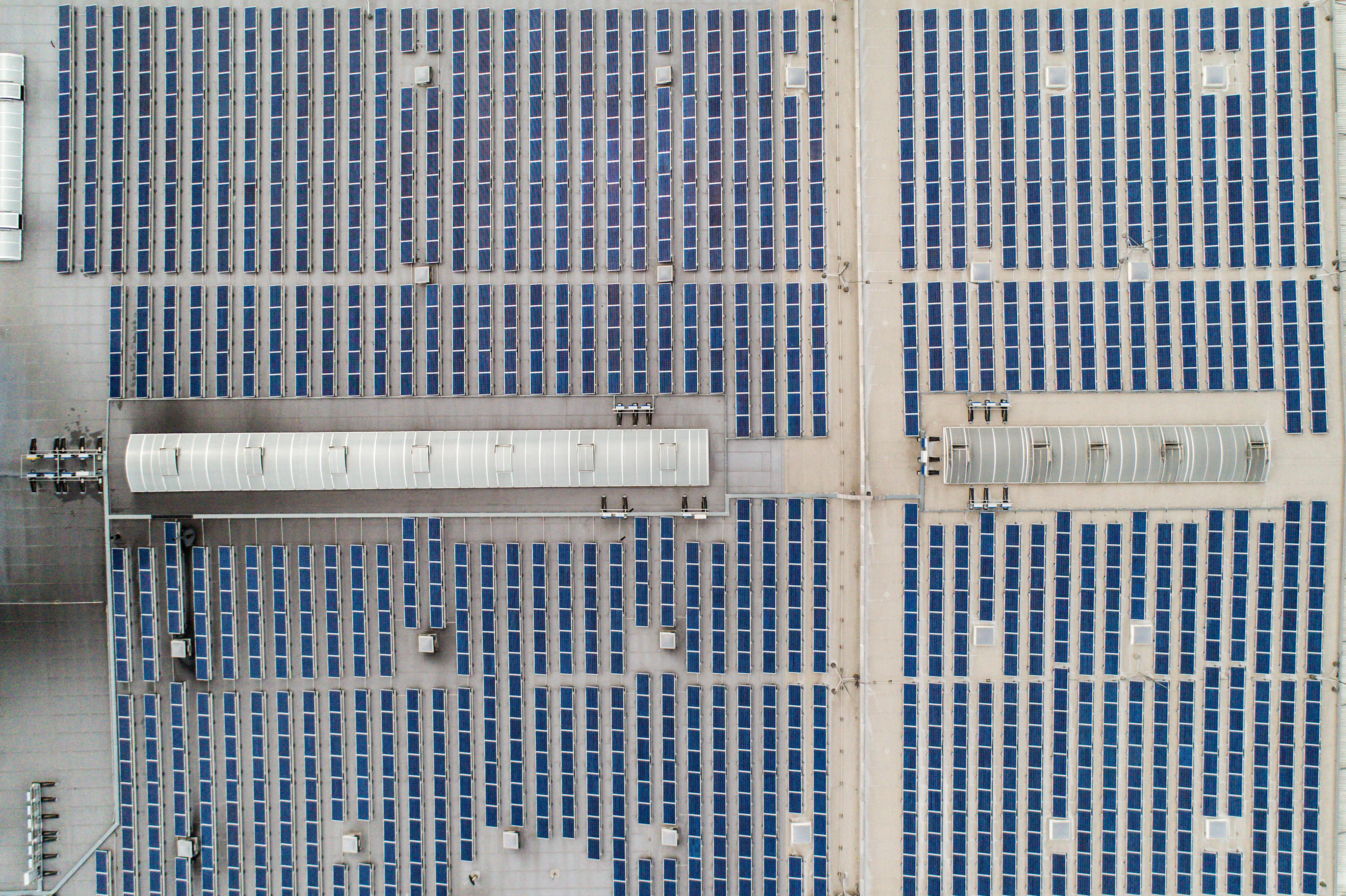 Aerial top down view on many Solar panels rows lined up on of factory roof.
